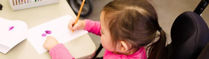Little girl in a wheelchair at a table writing on a paper with pencil