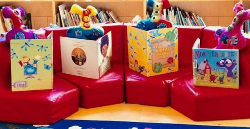 Stuffed abstract felted monsters reading picture books on red couch