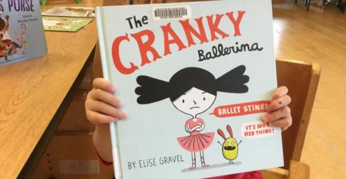 Kindergarten student holding up the Cranky Ballerina picture book by Elise Gravel