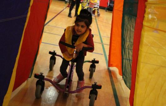 Student in a walker going through a tunnel during a relay race.