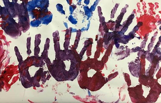 Painted children hand prints with hearts in the middle of their palm